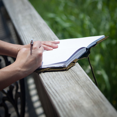 Person writing in blank page notebook outdoors