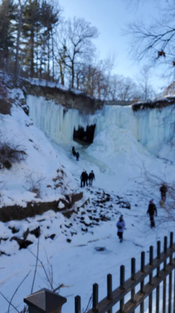 "Frozen waterfall with people walking ""into"" the waterfall."
